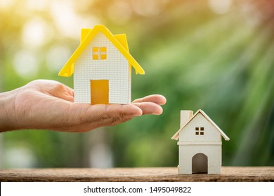 Man hand hold a new home put on the old house in the public park, Business investment the real estate concept.