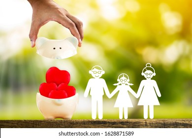 Man hand hold open the piggy bank and red hearts and family with paper cut put on the wood on the sunlight in the public park, Saving money for buy health insurance to the loved ones concept.