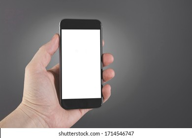 Man hand hold smartphone on gray background. Copy space