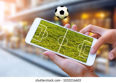 man hand hold and touch screen smart phone or cellphone with football field on screen over blurred pub and restaurant  ,Image to sport football or soccer online gambling