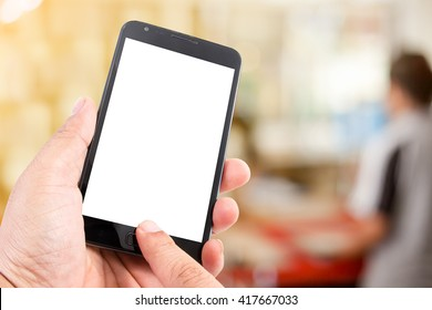 Man hand hold touch screen smart phone in the workspace..