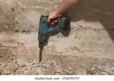 A man hand holding a battery hammer dril. Removin plaster with a battery hammer drill. Old moldy concrete plaster,