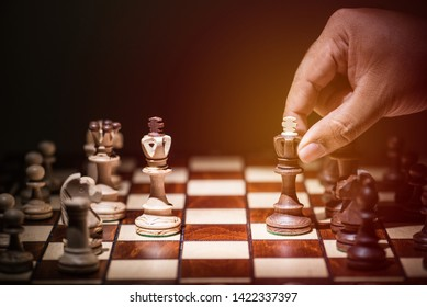 man hand holding black against white king chess pieces on chess board