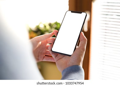 Man hand holding the black smartphone with big blank screen and modern frame less design in home interior, living room - isolated on white background angled position