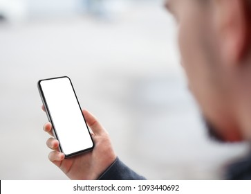Man hand holding the black smartphone with big white blank screen mockup, modern frame less design, isolated on blurred background. View from above the shoulder