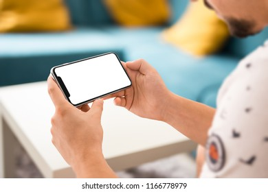 Man hand holding the black smartphone with big blank screen and modern frame less design in home interior, living room - isolated on white background horizontal position