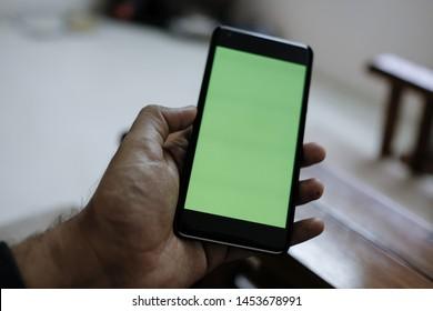 Man hand holding the black smartphone   green screen