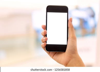 Man hand holding blank smart phone on tiled floor background, typing message or checking newsfeed on social networks