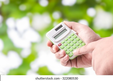 Man hand holding with calculator on Green bokeh background