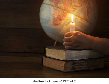 man hand holding candle light on stack of old books or holy bible over blurred of world globe in the dark room can be used for christian background that show Jesus is the light of the world