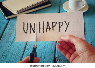man hand holding card with the text unhappy, cutting the word un so it written happy.  retro style image