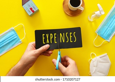 man hand holding card with the word expenses. cutting costs concept during covid-19 coronavirus outbreak.