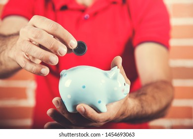 man hand holding coin with piggy bank
