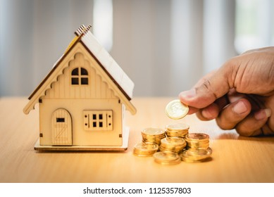 Man hand holding coins, inscriptions and symbols of the house. With increased savings for homebuyers and business loans.