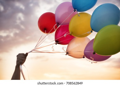 Man Hand Holding Colorful Balloons And A Beautiful Sunset. Birthday Party Balloons