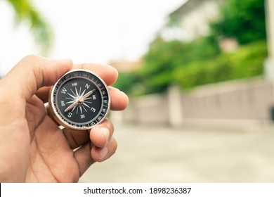 Man hand holding compass on city and car blurred background Using wallpaper or background travel or navigator image.