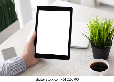 man hand holding computer tablet with isolated screen on table in room