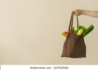 man hand holding cotton glocery bag with vegetables