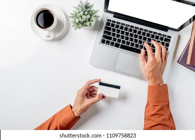 Man hand holding credit card and using laptop on white desk table with a lot of things.Top view with copy space,Flat lay.