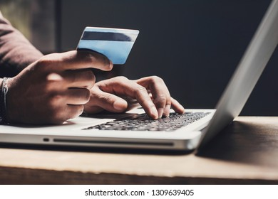Man hand holding credit card and using laptop. Businessman or entrepreneur working. Online shopping, e-commerce concept