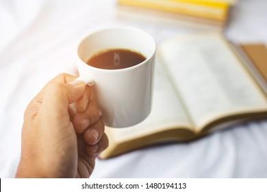 ้Close up of a man hand holding a cup of black coffee while reading a bible on bed, Christian background morning devotional concept with copy space