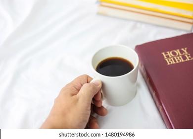 ้Close up of a man hand holding a cup of black coffee near holy bible on bed, Christian background morning devotional concept with copy space