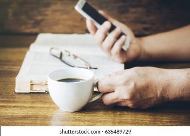 man hand holding a cup of coffee and smart phone over holy bible on wooden background