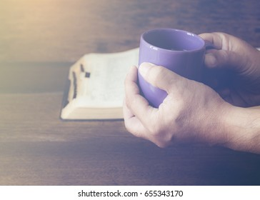 man hand holding a cup of coffee with blur open bible on wooden table in his devotional time