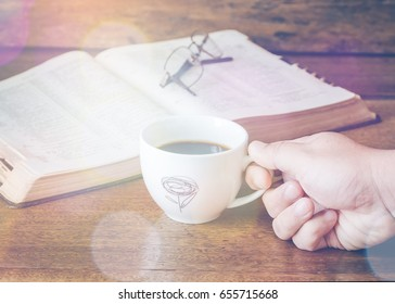 a man hand holding a cup of coffee with open bible on wooden table
