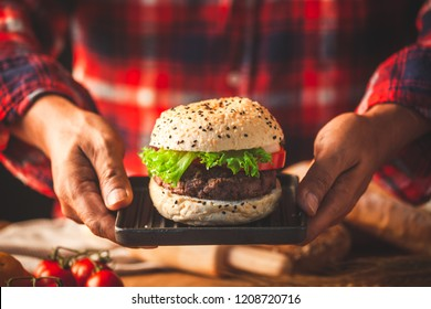 Man hand holding delicious homemade hamburger with fresh vegetables ready for serve and eat