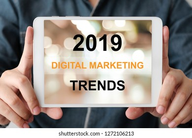 Man hand holding digital tablet with 2019 digital maerketing trends on screen background, digital marketing, business and technology concept