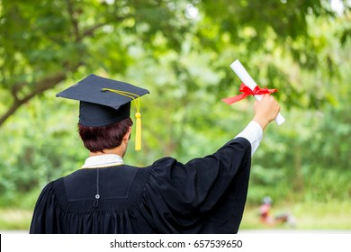 Man hand holding diploma with a red ribbon of graduate student.
