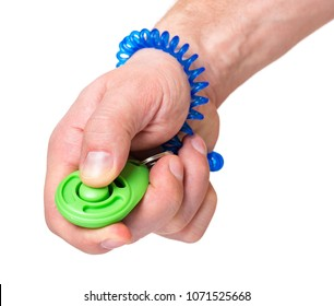 Man hand holding dog clicker - positive reinforcement training tool for dogs, isolated on white background. Clicker used for animal training.