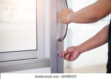 Man hand holding door element handle for open or lock the door or windows