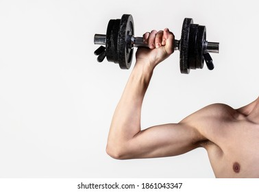 Man hand holding dumbbell in hand. Skinny guy hold dumbbells up in hands. A thin man in sports with dumbbells. Weak hand man lift a weight, dumbbells. Nerd maleraising a dumbbell.