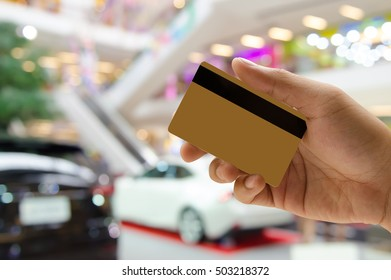 Man hand holding empty golden credit or debit card, member card, vip card with blurred background of new cars in showroom, or motor show event, credit card payment, car insurance concept.