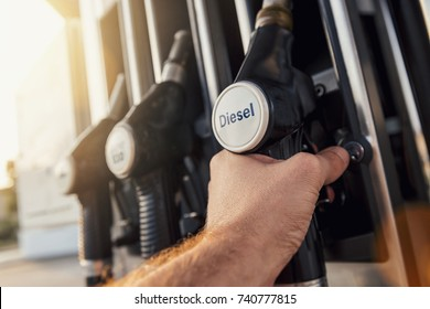 Man hand holding gas pump nozzle