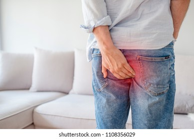 Man hand holding her bottom because having Abdominal pain and Hemorrhoids, Health care concept. Man with hemorrhoids and constipation.