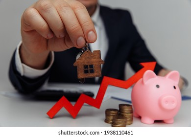 Man hand holding house key close-up. Red arrow and stack of coins money. Business investment and real estate concept