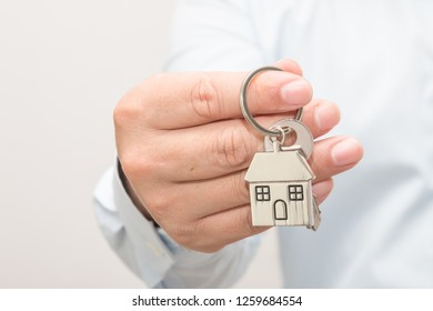 Man hand holding house model and key