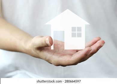man hand holding a house ,holding house representing home ownership and the Real Estate business, family protection and personal loans background