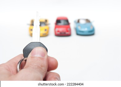 Man hand holding a key and pointing to a fleet of cars