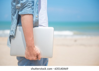Man hand holding laptop at the beach, working outdoor in summer season, digital nomad lifestyle concepts