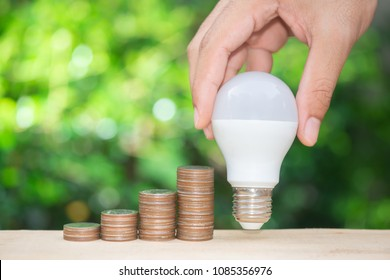 Man hand is holding the LED bulb site of the growing coins stack with green nature background for concept of saving energy
