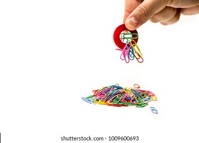 man hand holding magnet attracting metal paper clips