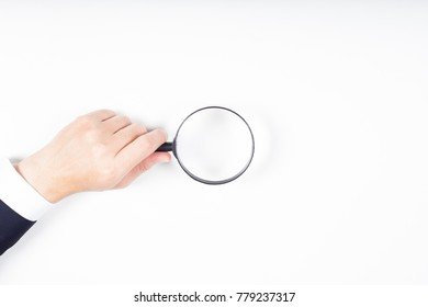 A man hand holding magnifying Glass on white background.