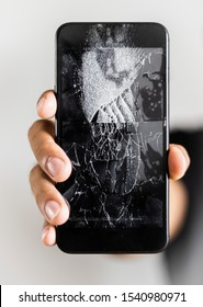 Man hand holding mobile phone with broken screen