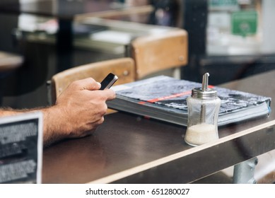 Man hand holding a mobile phone at the cafe