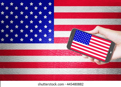 Man hand holding mobile smart phone with United States flag