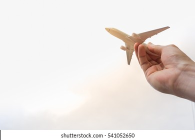 man hand holding a model plane with sky background